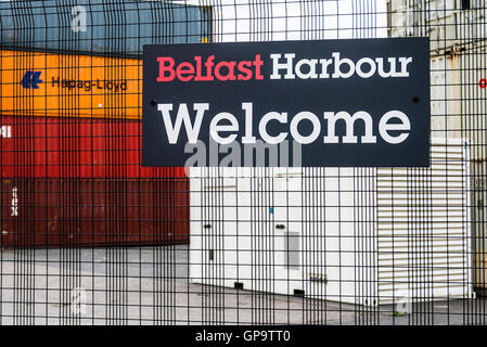 Shipping containers stacked up at Belfast Harbour, behind a security fence. - Stock Photo