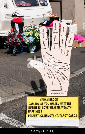 A gypsy palmreader places a sign outside her caravan advertising fortune teller services. - Stock Photo