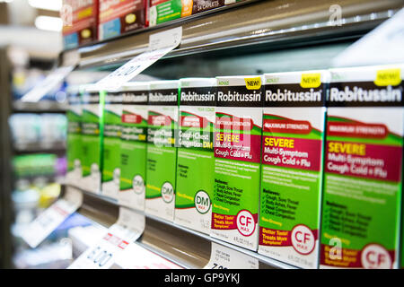 rows of Robitussin cough medicine boxes on a shelf at a store. - Stock Photo