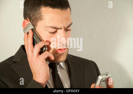 Young man using two mobiles phones. - Stock Photo