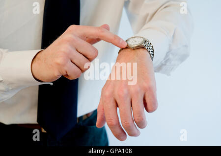 Man's hand pointing his watch. - Stock Photo