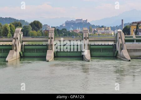 The Salzach hydroelectric power plant in Salzburg, Austria. Old town of Salzburg with fortress Hohensalzburg in - Stock Photo
