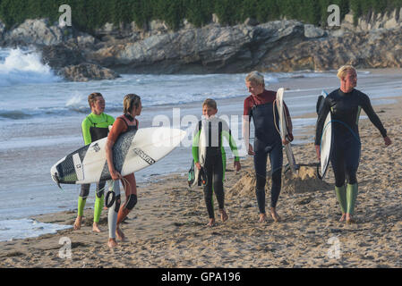 A group of five young Cornish surfers from Newquay finish their surfing session at Fistral in Newquay, Cornwall. - Stock Photo