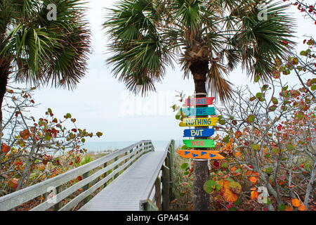 Colorful signs leading to the beach on the Gulf Coast of Florida encourage travelers to not leave any items. - Stock Photo