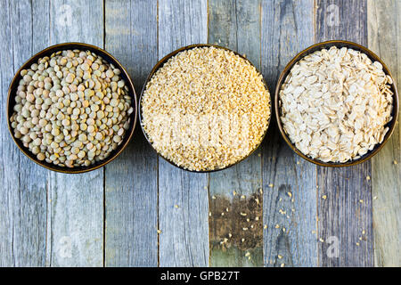 Bowls of lentils, bulgur and rolled oats in a row viewed from above on an old wooden table. - Stock Photo