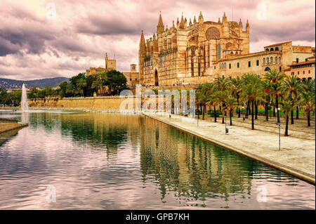 La Seu, the cathedral of Palma de Mallorca, reflecting in the water on sunset, Spain - Stock Photo