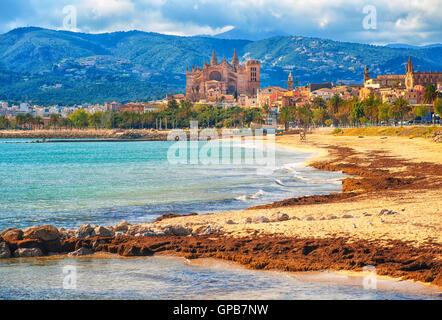 Sand beach in Palma de Mallorca, gothic cathedral La Seu in background, Spain - Stock Photo