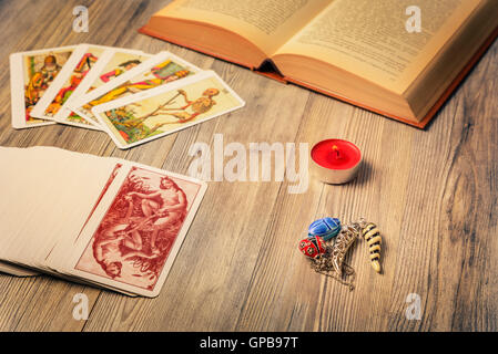 Composition of esoteric objects,candle,Tarots and book used for healing and fortune-telling,vintage style. - Stock Photo