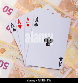 Four aces on top of some 50 euro banknotes - Stock Photo