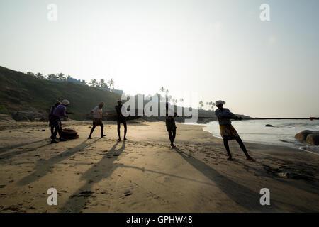Fishermen hauling in nets at sunrise, Vizhinjam Beach, Kovalam, Kerala,India, Asia - Stock Photo