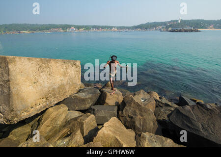 Fisherman with fish in his hand. A view from Vizhinjam, Kerala, India. - Stock Photo