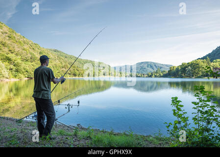 Fishing adventures. Fisherman is fishing on the banks of a lake - Stock Photo