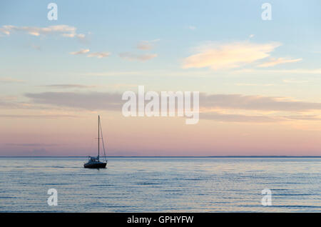One lone sailboat in calm water by late evening - Stock Photo