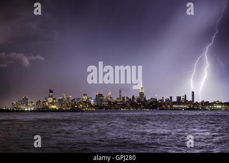 Lightning hitting a New York City skyscraper at twilight. Stormy skies over Midtown West Manhattan from the Hudson - Stock Photo