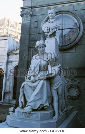 Sculpture of a mother and her child seated before an elderly lady at the Recoleta Cemetery, Buenos Aires, Argentina - Stock Photo