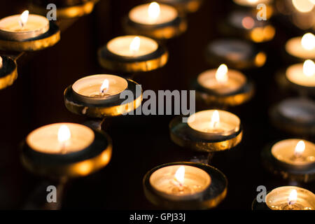 Rows of lit church candles remembering the dead and loved ones. - Stock Photo