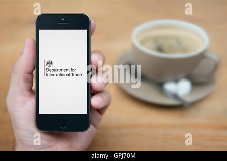 A man looks at his iPhone which displays the UK Government Department for International Trade logo (Editorial use - Stock Photo