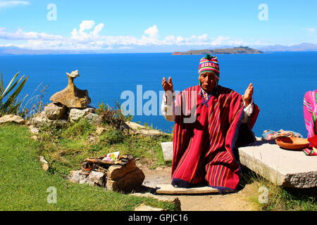 Making an offering to the Pachamama on Sun Island, Lake Titicaca - Stock Photo