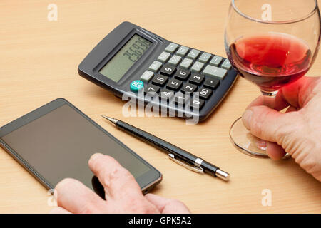 Man sitting at table with a calculator and a glass of red wine with his smart phone to the side - Stock Photo