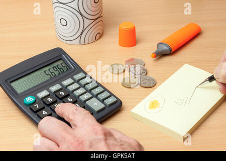 Man sitting at table working out what to do with his last bit of money - Stock Photo