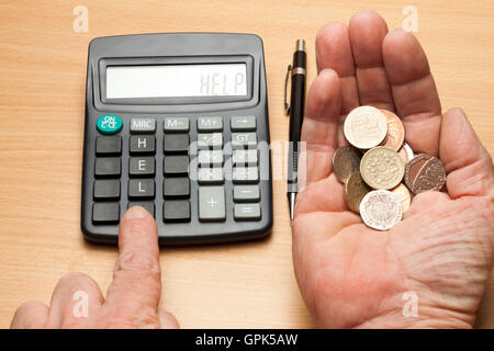 Man sitting at table with a hand full of loose change seeking help with a calculator - Stock Photo