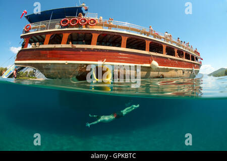 March 3, 2016 - Split level, man diving next to the tour boat, Cleopatra island (Sedir Island), Aegean Sea, Turkey - Stock Photo