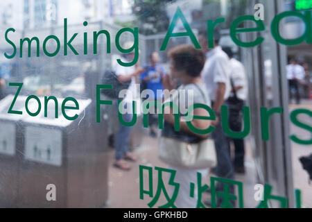 People smoke in a designated smoking area outside Shibuya station on September 5, 2016, Tokyo, Japan. The Japanese - Stock Photo