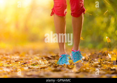 Close up of feet of woman runner running in autumn leaves, concept of training exercise - Stock Photo