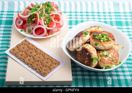 Top view on homemade fried meatballs in a white bowl, salad of raw vegetables and whole wheat hardtack on a green - Stock Photo