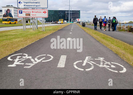 Cycle track and pedestrian footway with bicycle signs painted on tarmac surface along the waterfront. Reykjavik, - Stock Photo