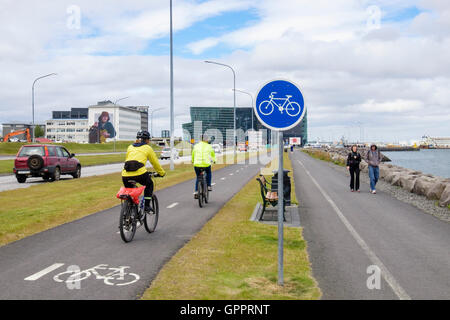 Cyclists riding on cycle track beside pedestrian footway with bicycle sign on the waterfront promenade. Reykjavik, - Stock Photo