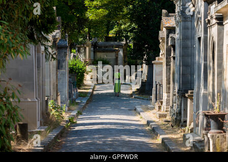 Woman in a green dress walking in pere lachaise cemetary - Stock Photo
