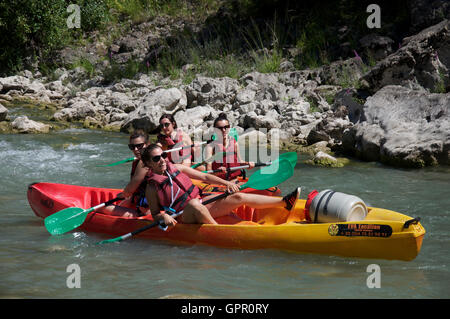 Tourism, water-sport. Four teenage girls having fun, messing about in canoes on the fast flowing waters of the River - Stock Photo