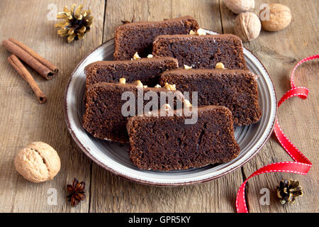 Chocolate sliced cake with nuts and spices for Christmas over rustic wooden background - Stock Photo
