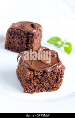 Chocolate mini cakes with chocolate icing and mint on white plate close up - Stock Photo