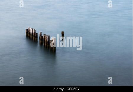 Wooden poles of an abandoned pier or jetty standing in the sea. Long exposure photography - Stock Photo