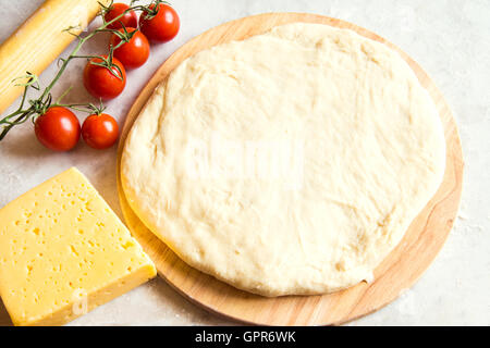 Dough on cutting board, tomatoes and cheese for pizza over white table - Stock Photo