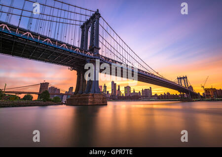 New York City at the Manhattan Bridge spanning the East River during sunset. - Stock Photo
