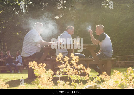 Smokers in a pub beer garden in Scotland, UK, surrounded by smoke - Stock Photo