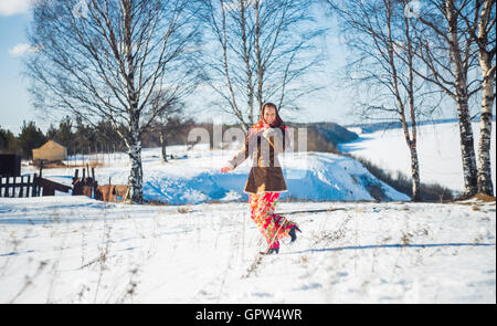 smiling young beautiful blond woman in russian winter suit runs through the snowdrifts. Girl clothed scarf, sheepskin - Stock Photo