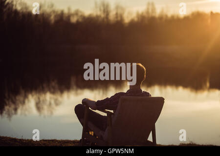 Man in the seat at bank of  lake also looks afar on sunset - Stock Photo