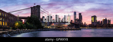 A colorful twilight view of the Brooklyn Bridge and the Manhattan skyline see from Empire Fulton Ferry Park in Brooklyn, - Stock Photo