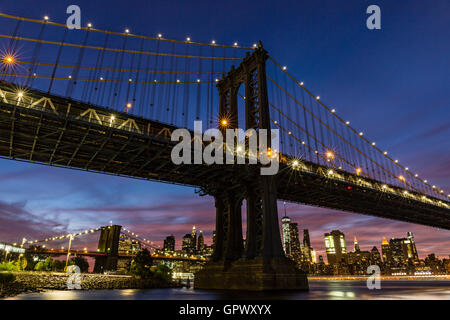 A colorful twilight view of the Manhattan and Brooklyn Bridges, and the Manhattan skyline see from John Street Park, - Stock Photo
