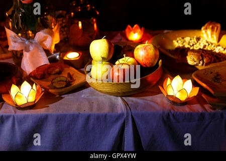 nocturnal wedding feast held in nature with enchanting lotus shape cande holders. - Stock Photo