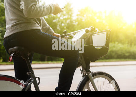 Man in casual clothes riding bike and focuses on phone - Stock Photo