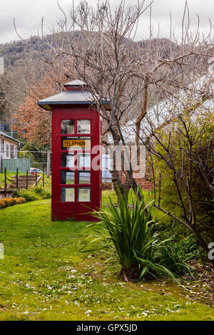 An old style red telephone booth in a grassy country lane - Stock Photo