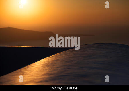 A warm sunset on the beautiful and romantic Greek Island of Santorini. Taken from one of the many restaurants and - Stock Photo