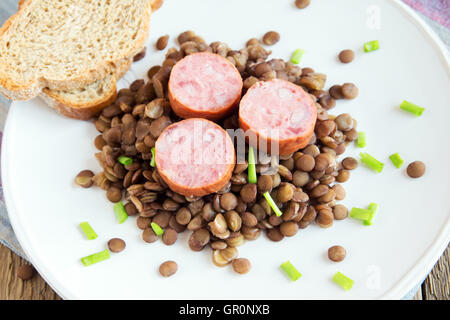 Green lentil with pork sausage (cotechino) on white plate - Stock Photo