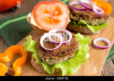 Vegetarian lentil burger with vegetables on wooden cutting board - Stock Photo
