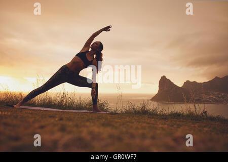 Full length shot of young woman practicing Utthita Parsvakonasana yoga asana. Healthy female exercising at sunset - Stock Photo